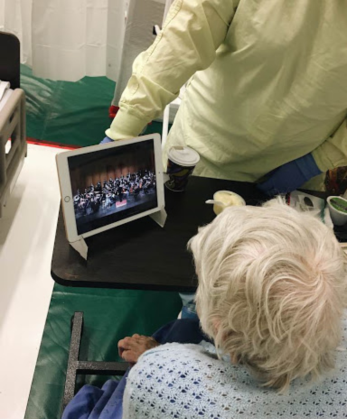 Senior patient watching a WSO concert from a tablet.